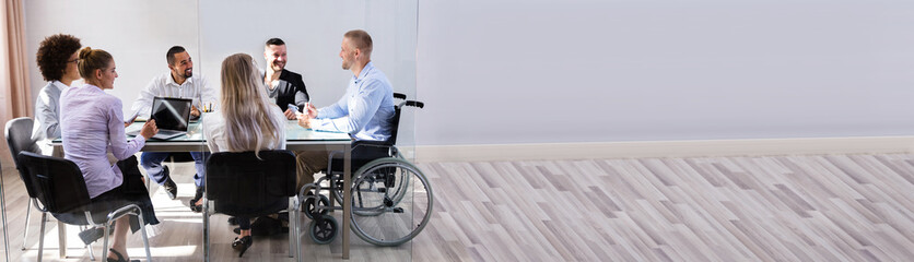 Disabled Manager Sitting With His Colleagues