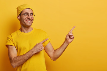 Friendly looking smiling man customer advertises sale on copy space right, points index fingers,...
