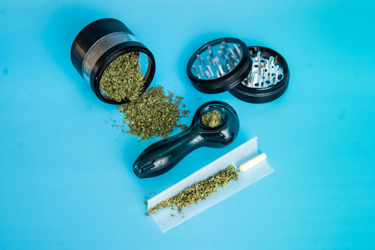 ground marijuana buds on a metal grinder. Ground Cannabis Flowers Before Use on blue Background
