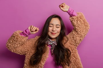 Happy brunette Asian woman dances, spreads hands up in air, enjoys music, makes cool movement, invites to join dancing with her, has romantic mood, tender look, wears warm coat, poses indoor