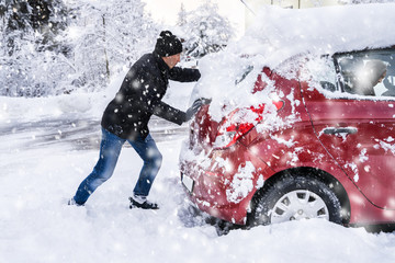 Man Pushing A Car Stuck In The Snow