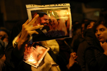 A woman holds a picture of newlyweds, victims of the crash of the Boeing 737-800 plane, flight PS 752, as people gather to show their sympathy in Tehran