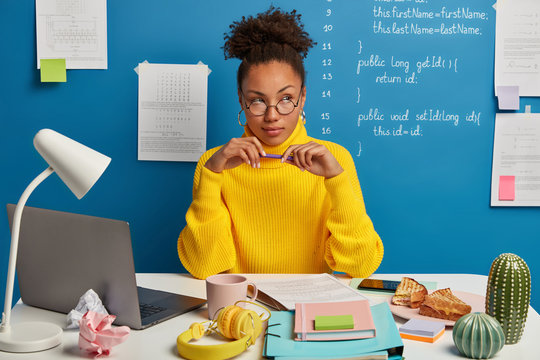Contemplative dark skinned woman in yellow sweater holds pen, works as professional programmer, thinks about installing popular application from internet, has e learning, break for having snack
