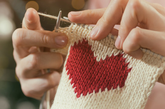 Concept of love and concern. Woman knitting the red heart for her loved one. Valentines postcard.