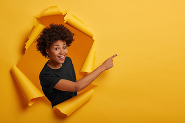 Photo sur Toile Les Textures African American woman in black t shirt, stands in paper hole, points away on blank space, stands in ripped paper, has cheerful expression, isolated over yellow background. Advertising concept