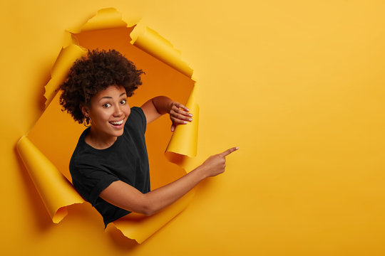 Pleased dark skinned Afro American woman stands in ripped background, laughs happily, poses in paper hole, points on right side, isolated on yellow wall. Space for your advertising or promotion.