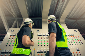 Two Electrical Engineer team working front control panel, Engineer training job with control panel in service room.