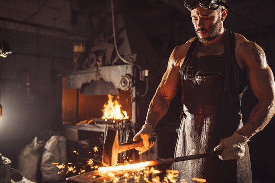 portrait of blacksmith in leather apron holding hot metal, wearing brown leather apron, space with furnace, fire