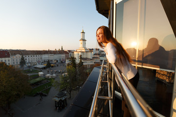 Young beautiful woman admiring panoramic view of european street architecture high from the balcony. Girl looking at street panorama on sunset. Fotomurales