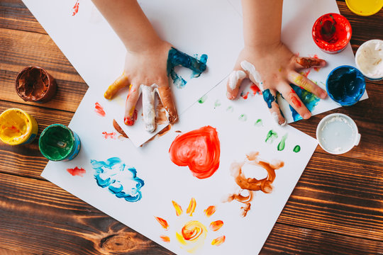 Close-up of child hand painting colorful mosaic. The child is drawing his palms on white sheets with finger paints