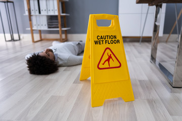 Man Falling On Wet Floor In Front Of Caution Sign