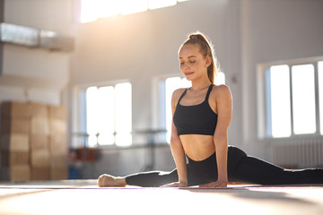Pretty satisfied female gymnast sits on splits, leans on hands, smiles gladly, expresses calmness, professional sport concept Fotomurales