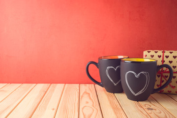 Valentines day concept with chalkboard coffee mugs, heart shapes and gift box on wooden table.