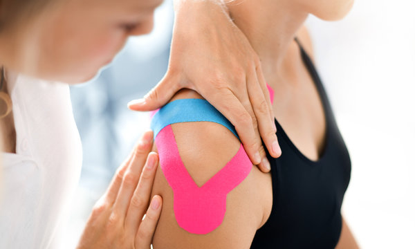 Kinesiology taping treatment with blue and pink tape on athlete patient injured arm. Woman hands apply kinesio treatment after sports muscle injury.
