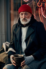 Senior caucasian homeless man sit begging for money. Nothing to live for. Dressed in street clothes.
