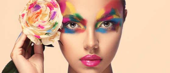 Beautiful girl model with multi-colored paints on her face. Woman with rose flower and bright color make-up. Cosmetics, beauty and makeup.  Spring and summer flowering  shopping Fotobehang