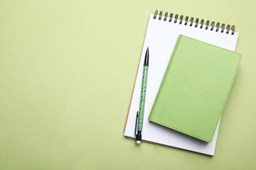 Stylish notebooks and pencil on light green background, top view. Space for text