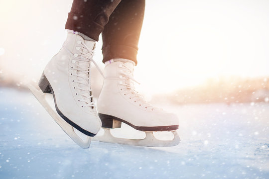 Winter active holiday concept. Girl is standing on ice in white figure skates, snow flakes, sunlight