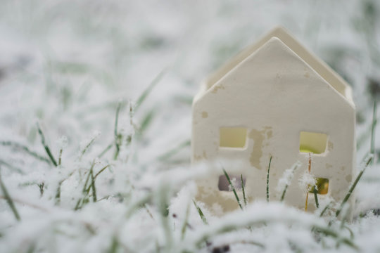 White toy house at winter landscape. Green grass covered snow. Eco house