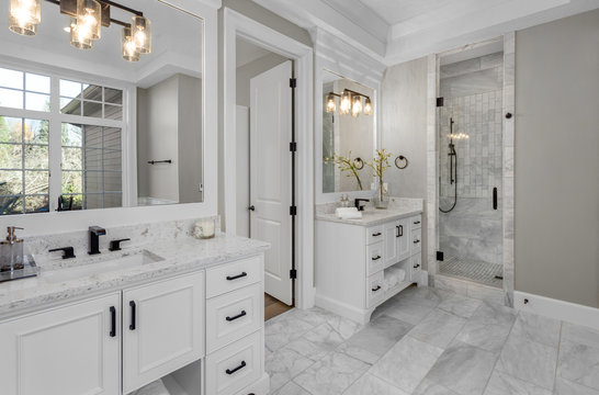 Beautiful bathroom in new luxury home with two vanities, sinks, and mirrors Shows shower with tile and wand