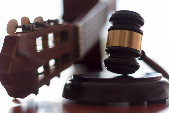 Judge's gavel and guitar. Concept of entertainment lawsuit, music piracy and copyright protection