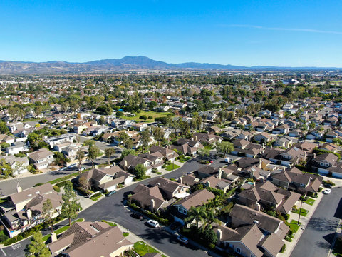 Aerial view of residential suburban packed homes neighborhood during blue sky day in Irvine, Orange County, USA