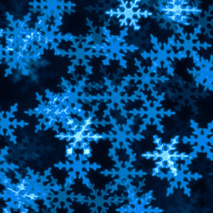 Abstract Christmas defocused snowflakes on black background made of bokeh lights. Classic blurred...