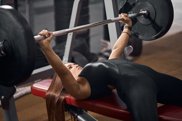 Professional female athlete dressed in black sportswear, lying on red bench, trying to lift iron heavy barbell, looking up with strong calm face, side indoor shot