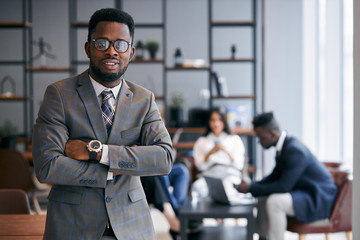 Personable man of african appearance wearing grey formal suit look at camera, in eyeglasses. After business meeting with multi-ethnic group of people in modern office