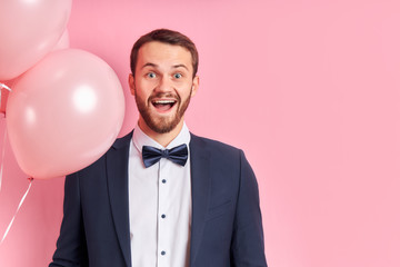 Good-looking man with beard wearing suir stand holding pink air balloons and happily smile,...