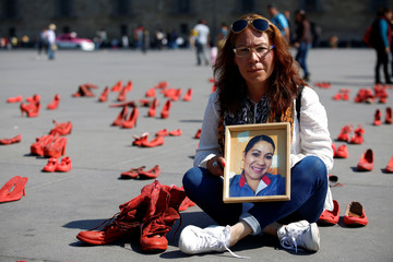 Elizabeth Machuca poses with a photo of her late sister Eugenia among pairs of women's red shoes, put on display by Mexican visual artist Elina Chauvet to protest against gender violence and femicide, at Zocalo square in Mexico City