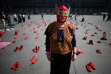 Mexican visual artist Elina Chauvet poses for a photo in front of pairs of women's red shoes, put on display by her to protest against gender violence and femicide, at Zocalo square in Mexico City