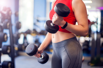 Woman in red top training bicep with dumbbels in gym. People, fitness and lifstyle concept