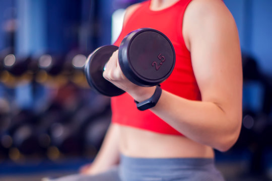 Woman in red top training bicep in gym. People, fitness and lifstyle concept