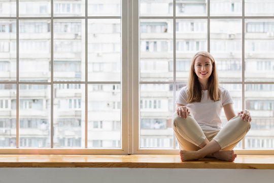 Young woman doing yoga in front of window. Happy woman practicing yoga while sitting on window sill in lotus pose asana