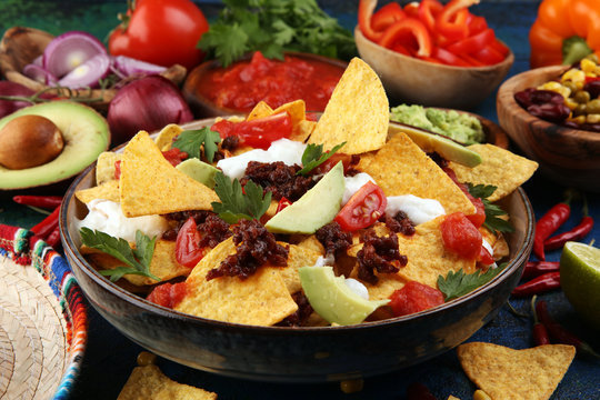 mexican nacho chips garnished with ground beef, guacamole, melted cheese, peppers and cilantro leaves in plate