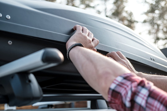 Hands cover the assembled, roomy trunk or cargo box on the roof of the car, before leaving for a family vacation.