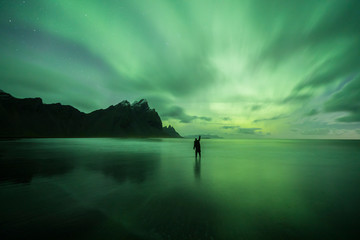 Aurora Borealis (Northern Lights) above a person at Stokksnes Beach and Vestrahorn Mountains, Iceland