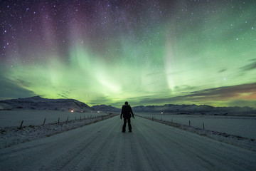 Northern Lights (Aurora Borealis) above a solo traveller on the road