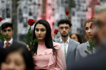 Attendees hold roses during a moment of silence for the plane crash victims of Ukraine International Airlines Flight 752 as Iranian Americans from across California converge in Los Angeles