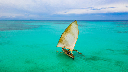 Aerial view of Fishermen on a sailing Pirogue departing Nosy Iranja in Madagascar