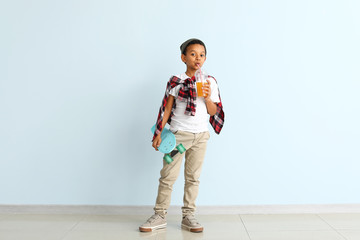Cute fashionable African-American boy with juice and skateboard on color background