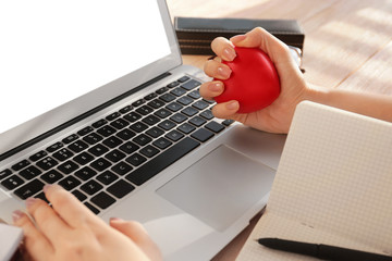 Woman squeezing stress ball while working with laptop in office