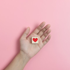Hands holding Wood cube with  red heart on pink background.