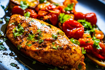 Roast chicken breast and vegetables on wooden background