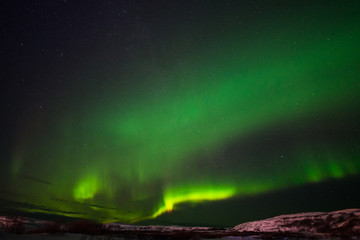 Tuinposter Noorderlicht hills, clear starry sky and colorful Northern lights, an incredible natural phenomenon