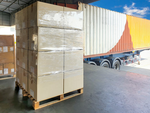 Stack of package boxes wrapping plastic on wooden pallet, truck container docking load cargo shipment, freight industry delivery logistics and transport.