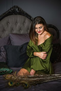 Woman in dark boudoir interior and silk green robe