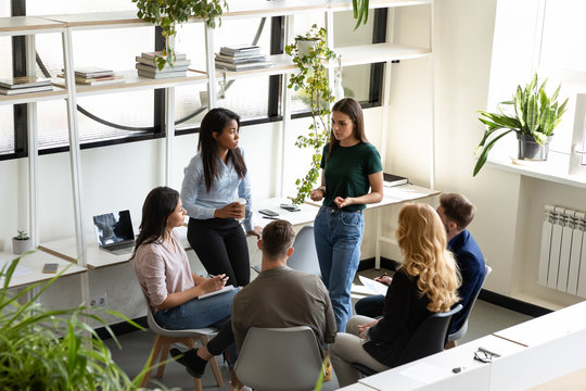 Concerned diverse office employees gather together solve business problems