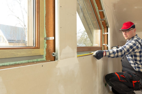 handyman making measurements for window sill for new installed pvc windows in a new build attic